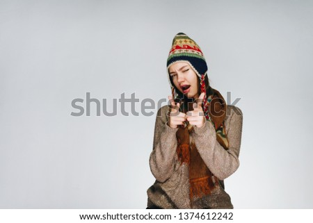 Funny woman in a Norwegian hat winks and points to the frame. Shows the success symbol