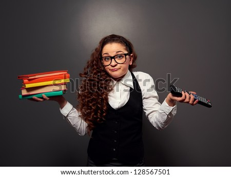 funny woman in glasses with pile of books and tv remote. picture over dark background