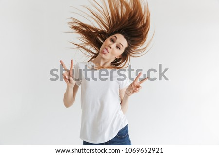 Funny woman in t-shirt showing peace gestures and her tongue while looking at the camera over grey background