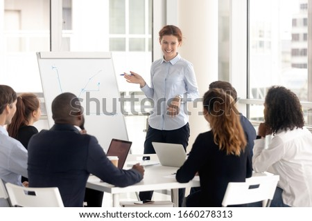 Funny woman leader consulting diverse group at meeting room, boss mentor coach at negotiation, corporate colleague training at boardroom.