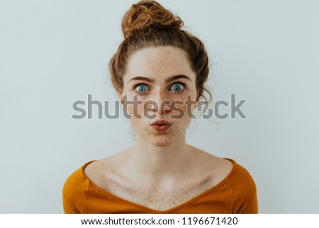 Funny woman portrait. Style. Beautiful blue eyed girl with freckles is pouting lips at camera, on a white background ストックフォト ©
