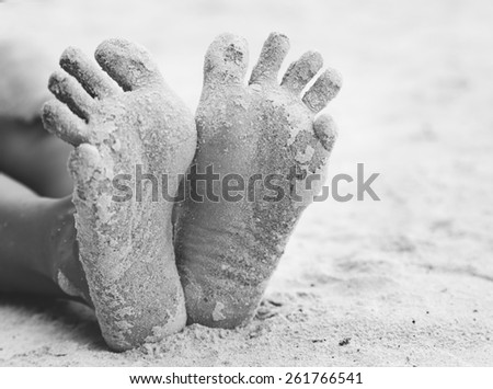 funny woman\'s feet on the white sand near the sea. Concept black and white
