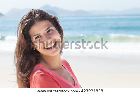 Funny woman with dark hair at beach with ocean and blue sky in the background