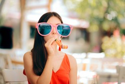 Funny Woman with Party Horn Blower and Oversized Sunglasses. Eccentric exuberant girl blowing a whistle at birthday party