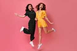 Funny women happily jump on pink background. Charming ladies in cool polka dot clothes and with curly dark hair have fun