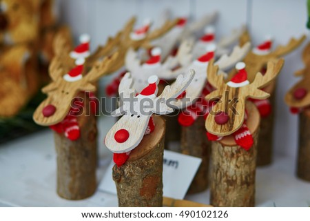 Funny wooden moose deers with red noses and Santa hats on traditional winter Christmas market in Munich, Germany #490102126