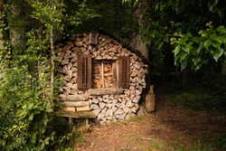 funny woodpile house in the middle of the green forest with a window and shutters and a bird house and a brown carnival mask with white teeth hanging in the window pane