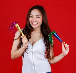 Funny young and cure Asian girl holding and playing party popers with funny and happy. Studio shot on red background.