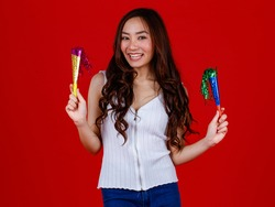 Funny young and cure Asian girl holding and ready to blow playing party popers with funny and happy. Studio shot on red background.