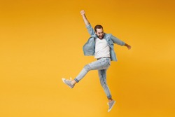 Funny young bearded man in casual blue shirt posing isolated on yellow orange wall background studio portrait. People sincere emotions lifestyle concept. Mock up copy space. Jumping, rising hands up