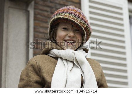 Funny young boy with long hair and hat outdoor in front of building.