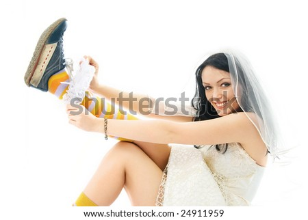 funny young bride wearing sporting shoes puts on a garter and smiles