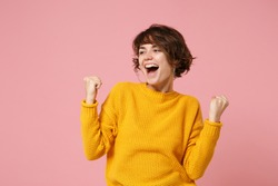 Funny young brunette woman girl in yellow sweater posing isolated on pastel pink background studio portrait. People lifestyle concept. Mock up copy space. Looking aside clenching fists like winner