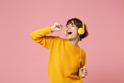 Funny young brunette woman girl in yellow sweater posing isolated on pastel pink wall background studio portait. People lifestyle concept. Mock up copy space. Listen music with headphones, sing song