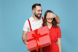 Funny young couple friends man woman in white red clothes hold present box with gift ribbon bow cover eyes with hand isolated on blue background. Valentine's Day Women's Day birthday holiday concept