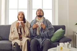 Funny young couple in warm hats, wrapped in blankets, sitting together on couch at home and sneezing in paper tissues. Sick husband and wife suffering from unpleasant symptoms of bad cold or flu virus