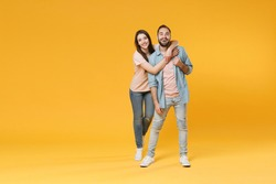 Funny young couple two friends guy girl in pastel blue casual clothes posing isolated on yellow wall background studio portrait. People lifestyle concept. Mock up copy space. Hugging, looking camera