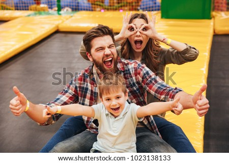 Funny young family with their little son spending time on a trampoline together at the entertainment centre