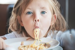 Funny young girl eating pasta