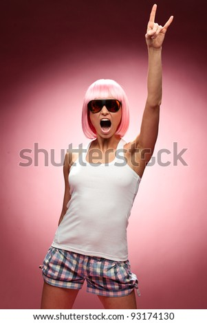 Funny young girl in pink wig and glasses dancing for camera across pink background