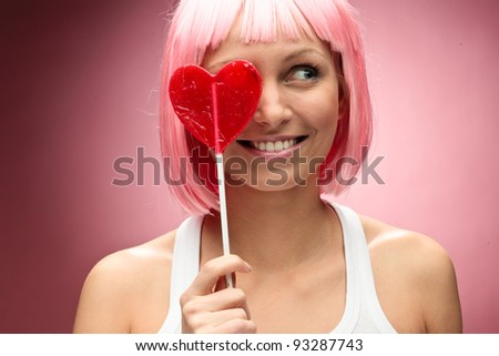 Funny young girl in pink wig holding lollipop and posing for camera across pink background