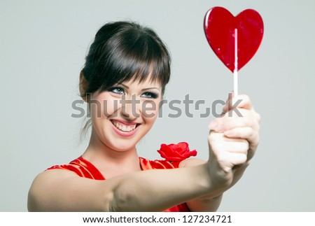 Funny young girl WITH lollipop and posing for camera across white background