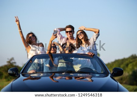 Funny young girls and guys in sunglasses are sitting in a black cabriolet on the road holding their hands up and making selfie on a sunny day.