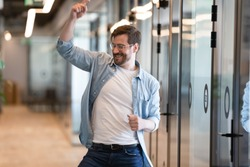 Funny young male worker standing in modern office hallway dancing moving feels overjoyed, concept of celebration career or salary growth, professional work achievements, promotion got vacancy of dream