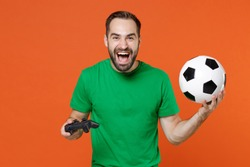 Funny young man football fan in green t-shirt cheer up support favorite team with soccer ball play pc game with joystick console isolated on orange background. People sport leisure lifestyle concept