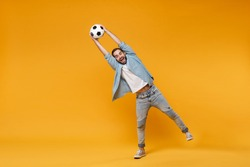 Funny young man in casual blue shirt posing isolated on yellow orange wall background, studio portrait. People sincere emotions lifestyle concept. Mock up copy space. Catching soccer ball in air