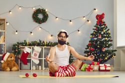 Funny young man in Santa cap and holiday costume sitting on fitness carpet and meditating over decorated home with Christmas tree at background. Christmas and New Year at home concept
