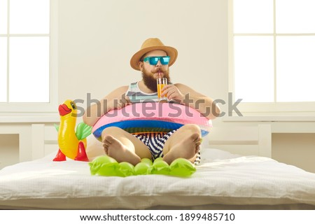 Funny young man in sunglasses and summer wear sipping beach cocktail, sitting barefoot in inflatable lifebuoy at home. Covid-19 quarantine, vacation in lockdown, canceled holiday travel plans concept Foto d'archivio ©