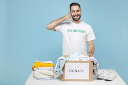 Funny young man in volunteer t-shirt stand near table with donation box clothes for needy doing phone gesture like says call me back isolated on blue background. Voluntary work help charity concept