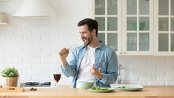 Funny young man singing song into whisk, cooking in modern kitchen, happy male holding kitchenware as microphone, listening to music, dancing, doing housework at home, preparing breakfast