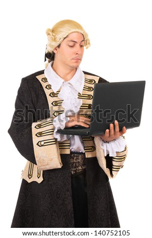 Funny young man wearing medieval costume and posing with a laptop. Isolated on white