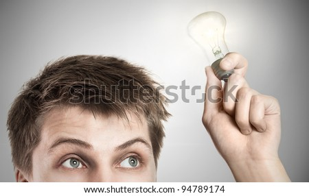 Funny young man with light bulb, on gray background
