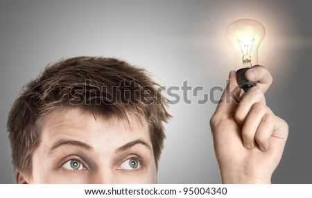 Funny young man with light bulb, on gray background - stock photo