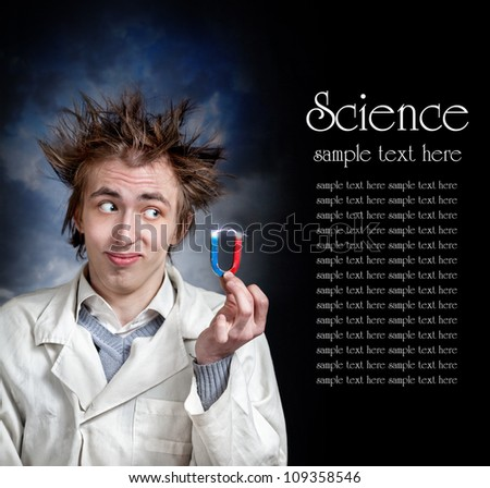 Funny young professor in white coat holding magnet with electricity lighting. Free space for your text