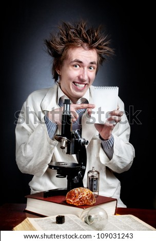 Funny young professor in white coat with microscope pointing at white blank notebook