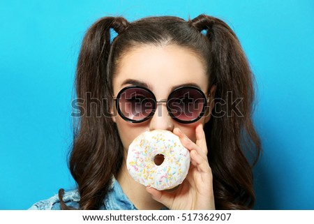 Funny young woman eating tasty donut on blue background #517362907