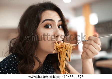 Funny young woman eating tasty pasta in cafe