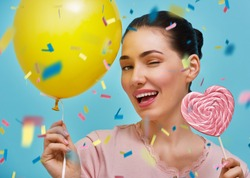 Funny young woman on background of bright blue wall. Beautiful girl is having fun with balloon, confetti and lollipop. Yellow, pink and turquoise colors.