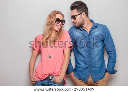 Funny young woman showing her boyfriend her tongue while he is looking at ther.