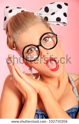 Funny young woman with pin-up make-up and hairstyle posing over pink background.