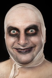Funny zombie with bandages around his head. Young man portrait with zombie make up