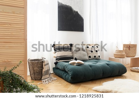 Fur and basket next to green futon with pillows in boho bedroom interior with poster. Real photo #1218925831