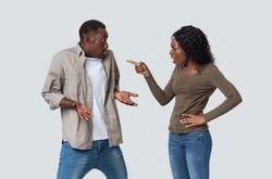 Furious african american young woman yelling and pointing at her innocent boyfriend. Angry black lady suspecting her husband in cheating, grey studio background. Distrust in relationships