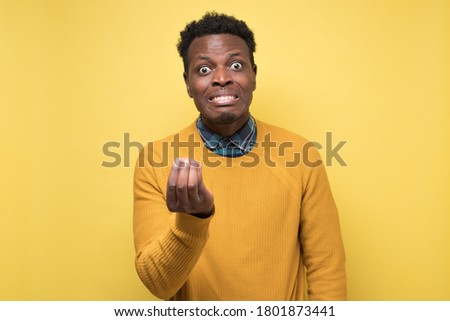Furious african man arguing with his friend showing italian gesture. Studio shot on yellow wall. Stock photo ©