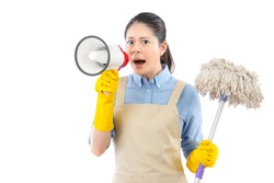 furious angry mad young woman using loud megaphone to announce her child to cleanup of the mess with holding a mop. isolated on white background. mixed race asian chinese model.