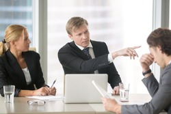 Furious boss scolding young frustrated intern, dismissing him with hand gesture. Ineffective stressed office worker receiving dismiss notification sitting at table, listen to irritated boss yelling